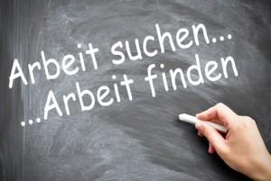 """Hand schreibt an eine Tafel mit Kreide """"Arbeit suchen .... Arbeit finden"""""""